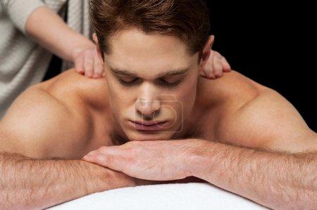 Man getting back massage in spa salon