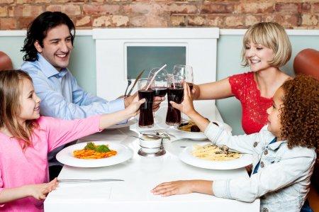 Family raising their glasses before eating