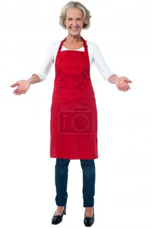 Photo for Smiling joyous aged female chef with open arms - Royalty Free Image