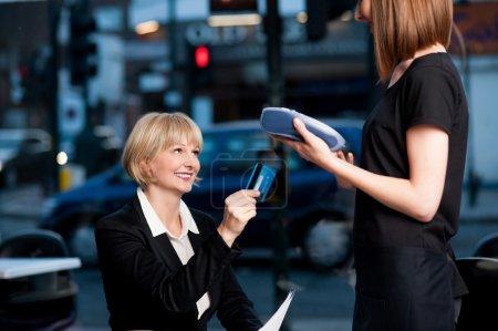 Firmenfrau schwenkt ihre Karte, um zu bezahlen