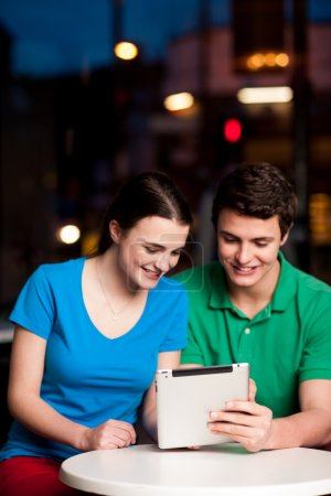 Photo for Happy young couple with a tablet computer in restaurant - Royalty Free Image