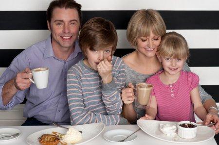 Photo pour Joyeuse famille caucasien de quatre s'amuser au restaurant - image libre de droit