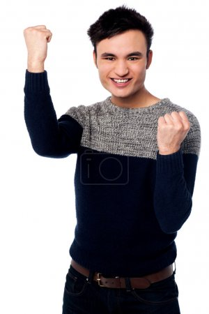 Excited young guy with clenched fists