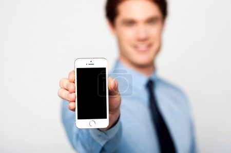 Young sales guy displaying cellphone