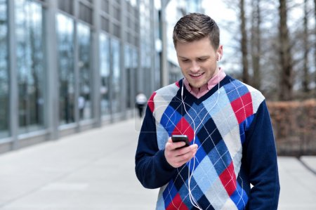 Photo for Happy young man listening to music on his mobile phone - Royalty Free Image