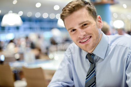 Smiling young man relaxing in restaurant