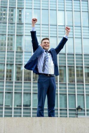 Emocionado hombre de negocios levantando sus brazos