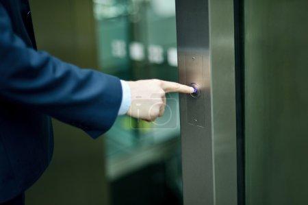 Photo pour Homme d'affaires en appuyant sur le bouton d'ascenseur - image libre de droit