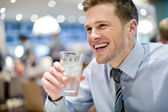 Smiling young man drinking water in cafe