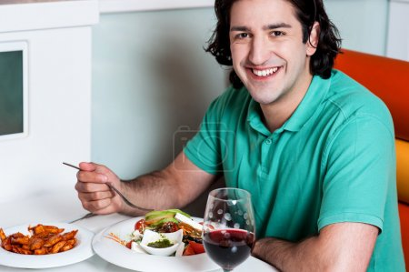 Young smiling man eating at restaurant