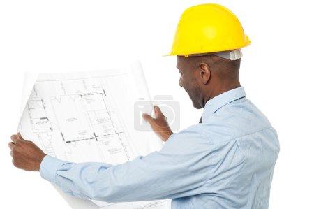 Photo pour Ingénieur de construction avec casque, revoir le plan de construction - image libre de droit