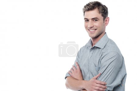 Photo pour Confiant jeune homme posant avec les bras croisés - image libre de droit