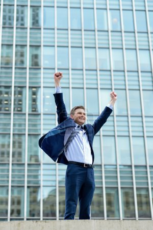 Excited businessman raising arms