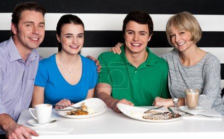 Photo pour Famille de quatre personnes appréciant leur petit-déjeuner ensemble - image libre de droit