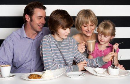 Photo pour Joyeuse famille de quatre personnes appréciant leur petit-déjeuner dans un restaurant - image libre de droit