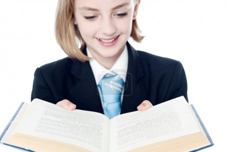 Smiling girl reading open book