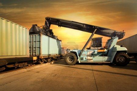Photo pour Grue levant conteneur au coucher du soleil - image libre de droit