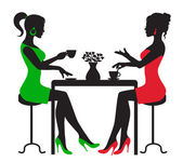 Silhouette two women drinking coffee at a table on a white background
