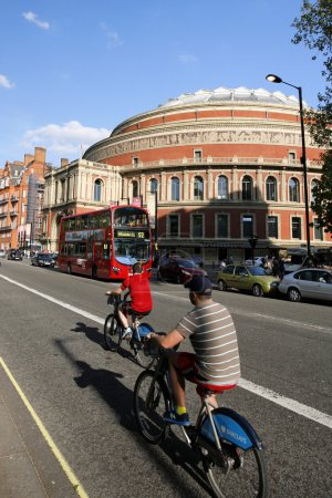 Tourists on rental bike, passing by Royal Albert Hall