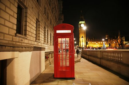 Photo for Red Telephone Booth at night, Big Ben in the distance. Red phone booth is one of the most famous London icons - Royalty Free Image