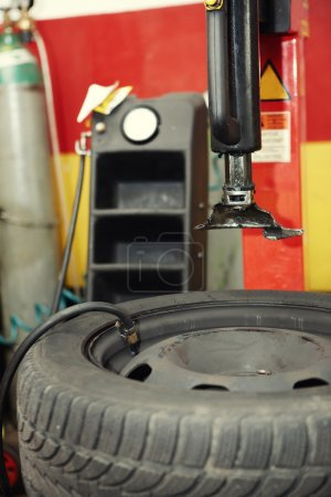 Photo for Inflating a tire in auto repair shop before mounting a wheel to the car - Royalty Free Image