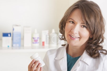 Young woman pharmacist with a bottle of drugs