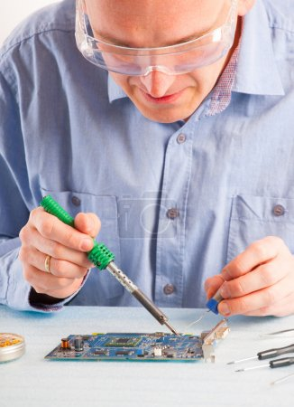 Photo for Man using soldering tool for the computer parts. - Royalty Free Image