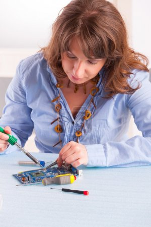 Photo for Woman using soldering tool for the computer parts. - Royalty Free Image