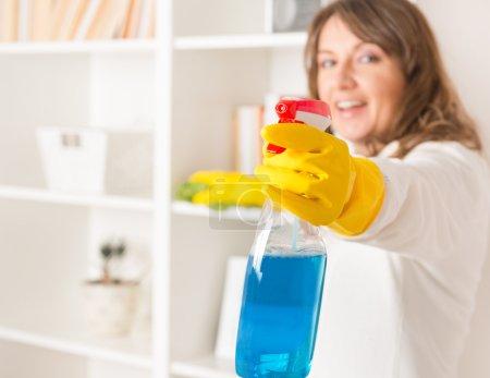 Photo pour Belle jeune femme, sa maison avec des gants jaunes avec vaporisateur nettoyant et un chiffon de nettoyage - image libre de droit