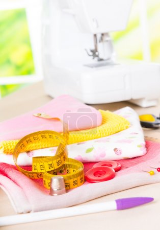 Photo pour Machine à coudre avec les tissus colorés, fils, boutons, dé à coudre et autres accessoires de couture. - image libre de droit