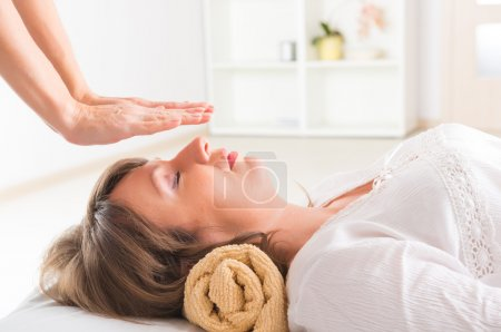 Professional Reiki healer doing reiki treatment to...
