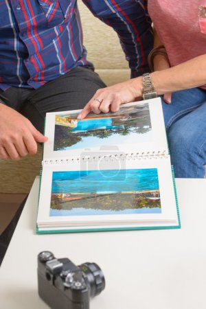 Foto de Pareja mirando fotos en un álbum de fotos en el sofá en casa - Imagen libre de derechos