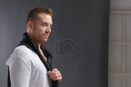 Photo for Cool looking man, wearing modern casual clothes posing over grey background - Royalty Free Image