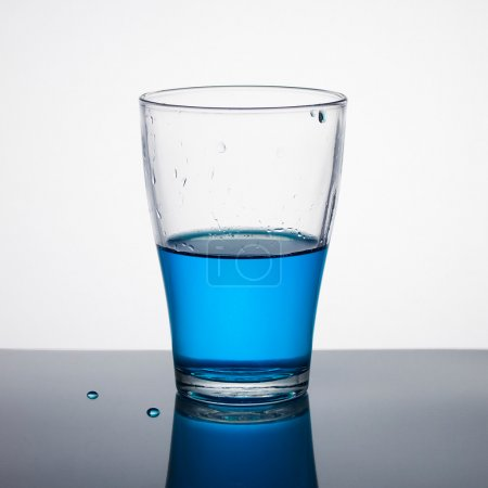 Glass half full of blue liquid