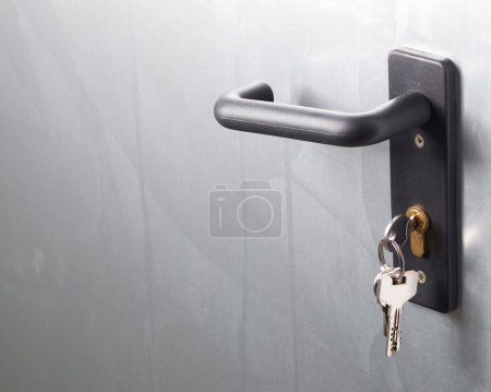 Photo for A door handle with lock and keys. The door is metallic. - Royalty Free Image