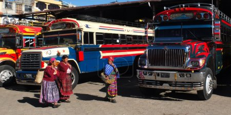 Three native women wearing traditional clothes walk near colored buses at the market