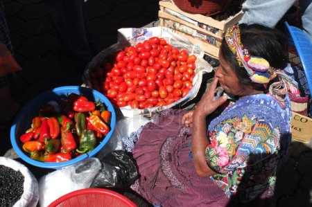 Vegetables vendor wearing a beautiful colored headdress at the market.