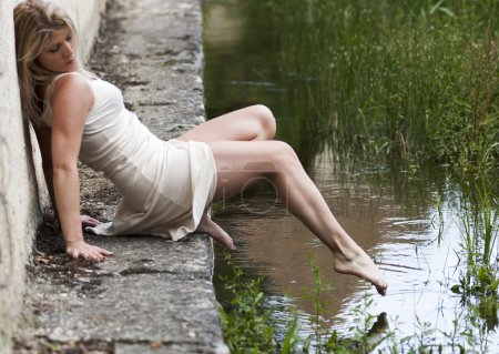 Photo for Blond woman sitting on the edge of a pond. She tries to touch the water with her toe. She wears a white dress. - Royalty Free Image