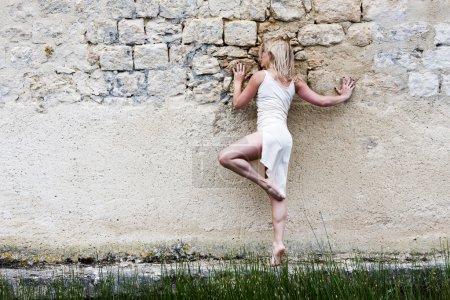 Barefoot blond girl along a wall.