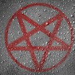 Pentagram symbol painted on metal surface covered ...