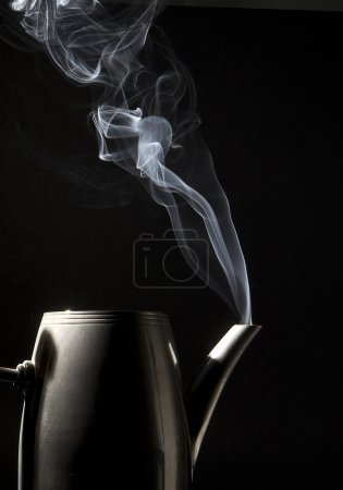Tea kettle with boiling water on black background...