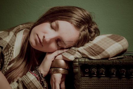 A beautiful teenage girl sleeping on a sound device