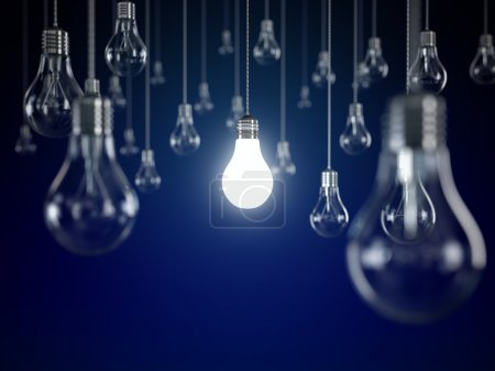 Photo for Hanging light bulbs with glowing one isolated on dark blue background - Royalty Free Image