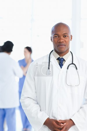 Doctor standing upright with his hands crossed and his team in t