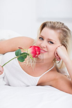 Young woman smelling a pink rose