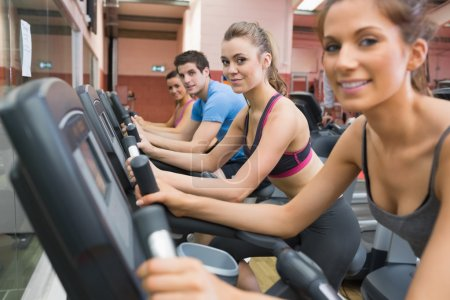 Four working out on exercise bikes