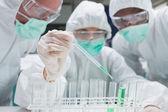 Chemik přidáním zelené tekutiny do zkumavky, další dva jsou zvláštní vztah