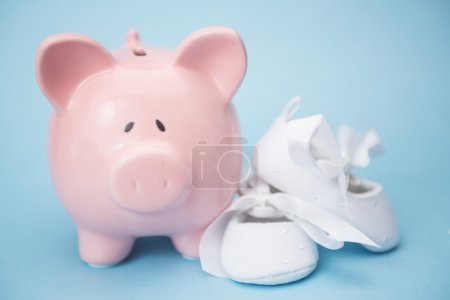 Piggy bank and white baby shoes