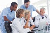 Usměvavá lékařský tým pomocí přenosného počítače