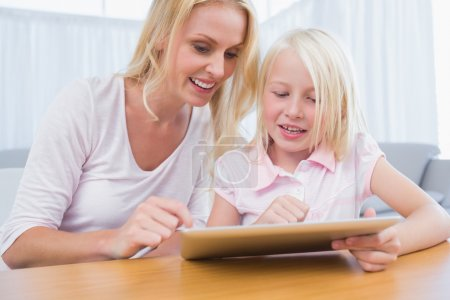 Cheerful mother and daughter using digital tablet